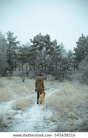 Girl walking a dog in the frozen winter woods