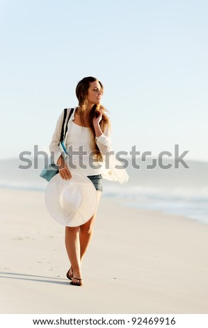 girl walking along the shoreline with beach hat and bag - stock photo