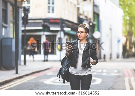 Girl walking down the street with her phone. A woman is walking alone in London. She is looking at her smart phone. Blurred on background there are  typical english houses and shops.
