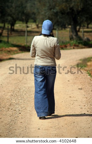 girl walking in a country road - stock photo