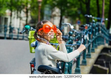 Girl walking in orange glasses for Dutch Queensday on the Amsterdam street - stock photo