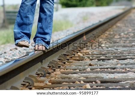 Girl walking in sandals across train tracks - stock photo