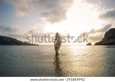 Girl walking in the water at sunset - stock photo