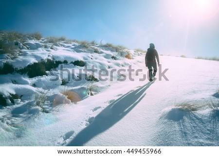 Girl walking in to sun light on winter track - stock photo