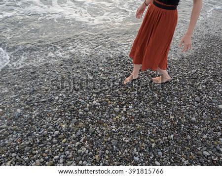Girl walking near the sea on the sand - stock photo
