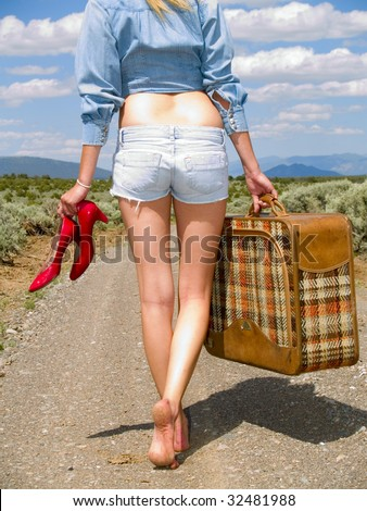 Girl walking on a dirt road with a suitcase carrying her red shoes.
