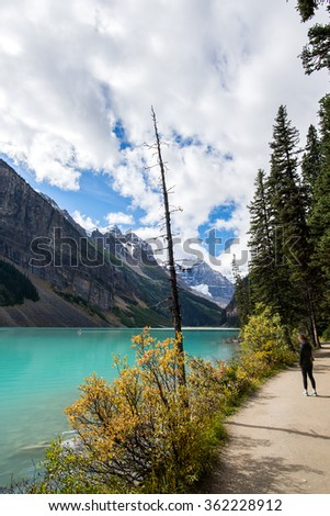 girl walking on a hiking at the turquoise water's edge of lake louise in the rocky mountains of alberta canada - stock photo