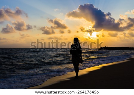 Girl walking on beautiful foggy beach at sunrise silhouette style - stock photo