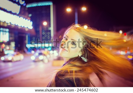 Girl walking on the night city street in slow motion (Note: this image is in motion, without still focus) - stock photo