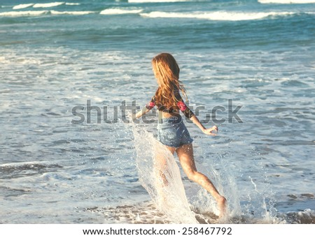 girl walking on the sea at sunset - stock photo