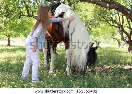 Girl walking with a charming pony in the apple garden/Pony in the meadow eating green grass - stock photo