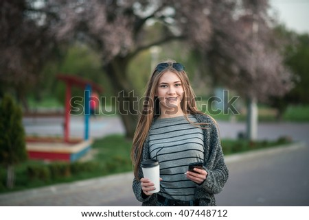 girl walking with coffee and phone