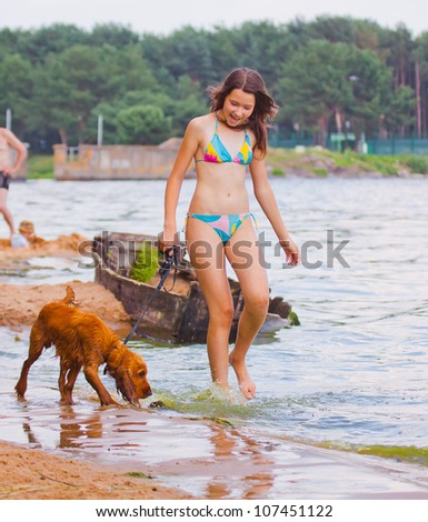 Girl walking with dog on beach, English Cocker Spaniel