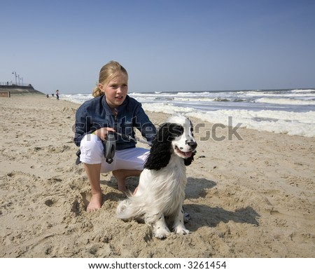 girl walking with her dog (at the bach, blue sky) - stock photo