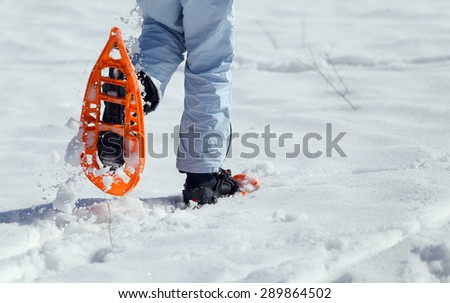 girl walking with two orange snowshoes in mountains - stock photo