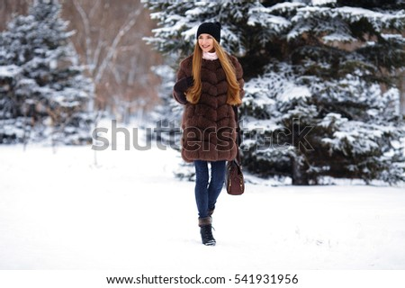 Girl walks along snowy street in fur coat and bag in his hand