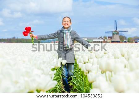 Girl walks between of the purple tulips field - stock photo
