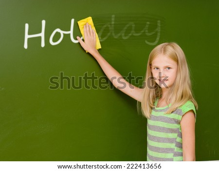 """girl washes away from the chalkboard word """"holiday"""" - stock photo"""