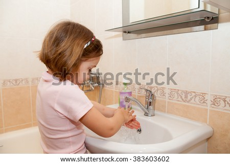 Girl washing hands with soap.