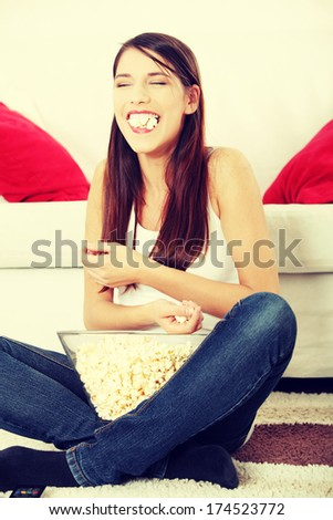Girl watching TV having fun eating popcorn. - stock photo