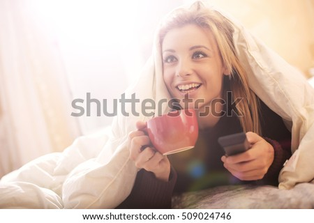 Girl watching Tv in bed