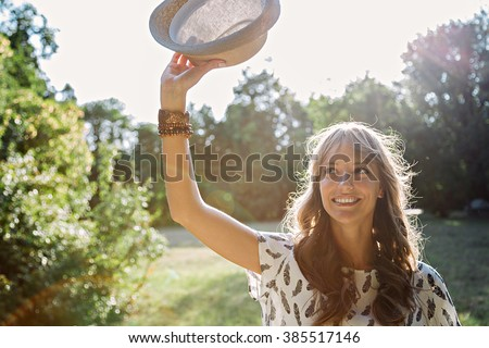 Girl waving with hat in forest - stock photo