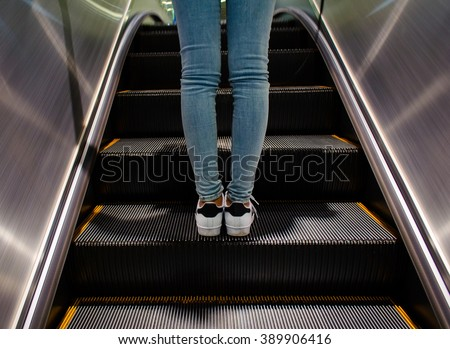 Girl wear sneaker riding on an escalator. - stock photo