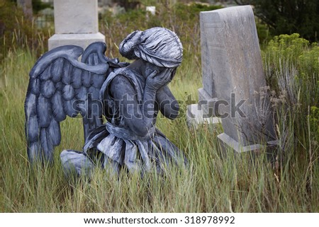 Girl wearing a home made life like angel costume in an old grave yard - stock photo
