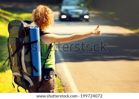 Girl wearing backpack holding map, hitch hiking. - stock photo