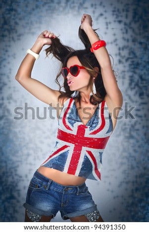 Girl wearing blouse with Britiain flag colors, heart shape glasses and dancing/Dance with Britain - stock photo
