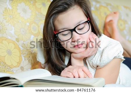Girl wearing glasses reading a book - stock photo