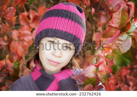 Girl wearing hat and scarf among colorful autumn leaves - stock photo