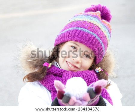 Girl wearing hat, scarf and mittens playing with snowball - stock photo