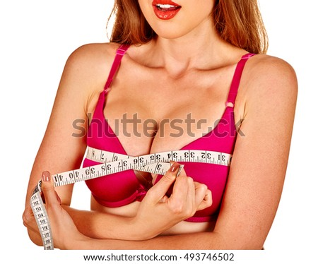 Girl wearing in bra measures her breast measuring tape. Girl wearing her new silicone breast implants.