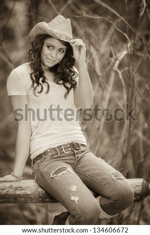 Girl wearing jeans sitting on the fence - stock photo