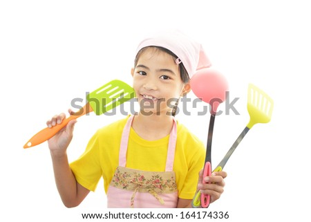 Girl wearing kitchen apron with cookware - stock photo