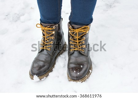 Girl wearing leather boots in snow