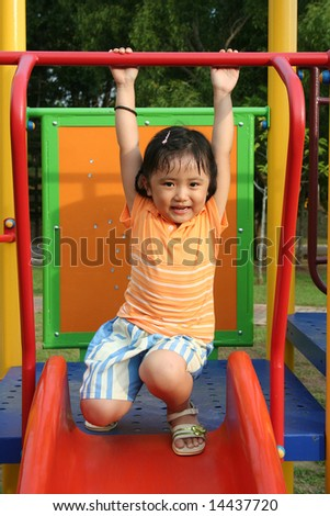 Girl wearing orange tee on the slides in the park - stock photo