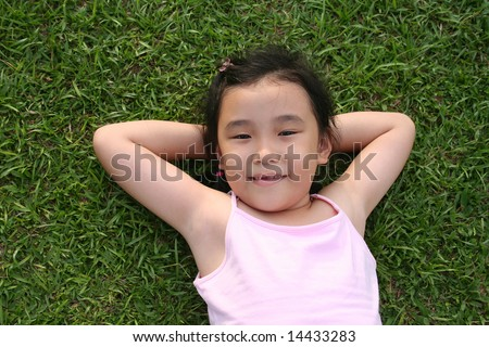 Girl wearing pink singlet lying on the grass