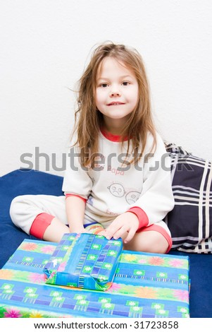girl wearing pyjamas sitting on a bed