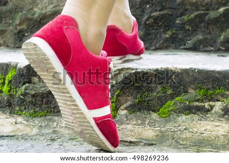 Girl wearing red shoes steps up.