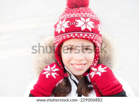 Girl wearing red winter hat and mittens - stock photo