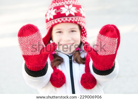 Girl wearing red winter hat and mittens showing her hands - stock photo