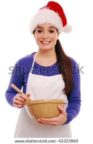 Girl wearing santa hat with mixing bowl - stock photo