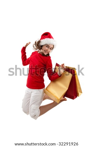Girl wearing Santa's Hat holding shopping bags jumping isolated on white background