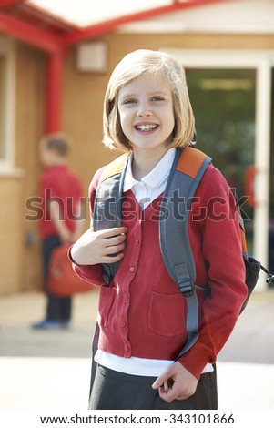 Girl Wearing School Uniform Standing In Playground - stock photo