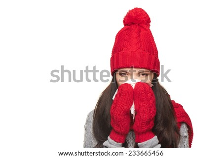 Girl wearing warm winter hat, scarf and gloves blowing nose with a handkerchief, over white background - stock photo