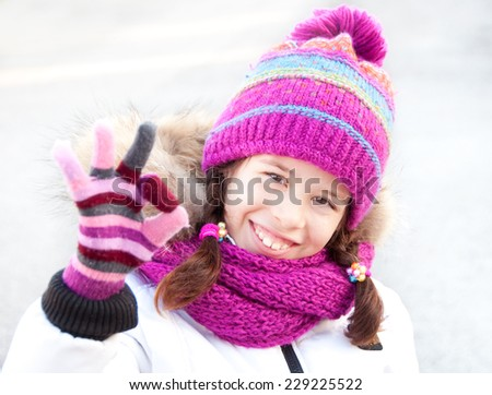 Girl wearing winter hat, scarf and gloves showing OK - stock photo