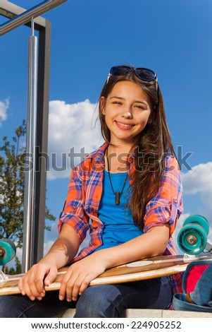 Girl wears sunglasses and sits with skateboard