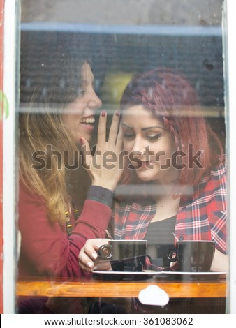 girl whispering into another girls ear while sitting by the window - stock photo